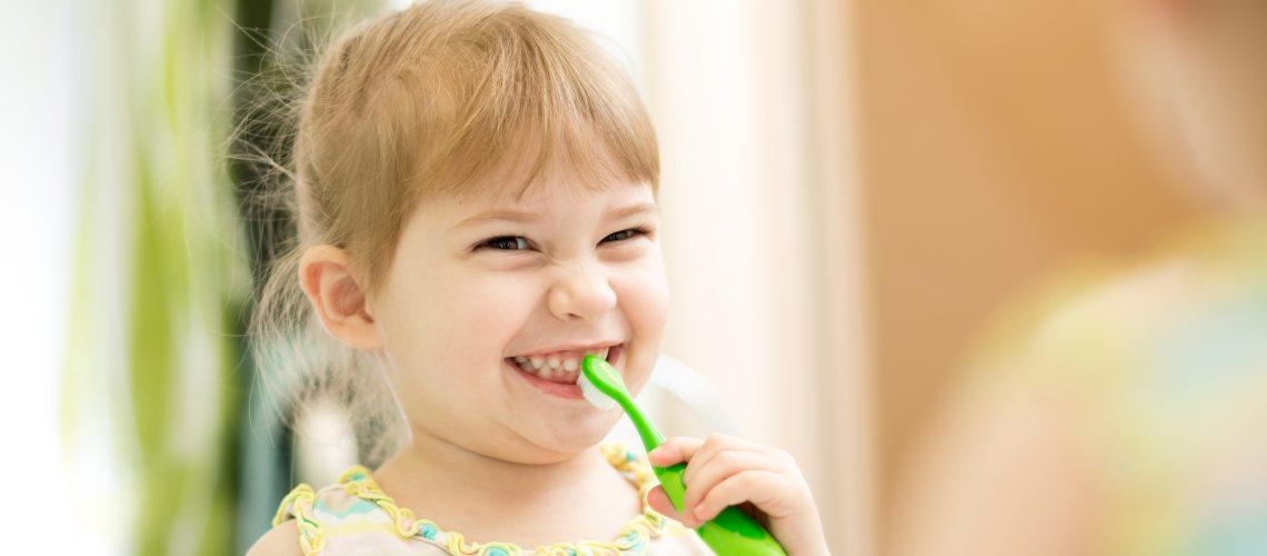 cute kid girl brushing teeth in bathroom